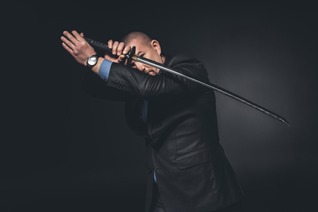 Man in suit fighting with katana sword on black