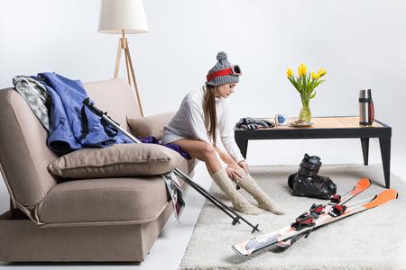 Young sportswoman wearing warm socks, ski equipment lying on floor