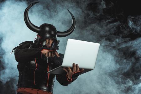 Armored samurai using laptop on dark background with smoke
