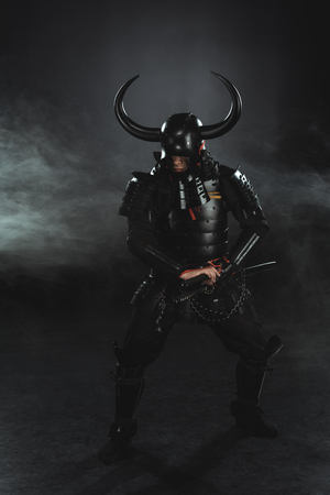 Armored samurai taking out his katana on dark background with smoke Banco de Imagens