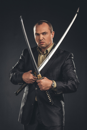 Angry man in suit with katana sword isolated on black 写真素材