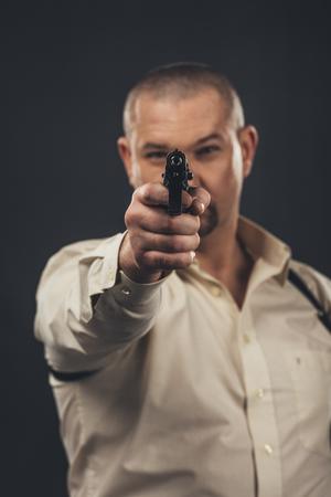 Homme dangereux visant l'arme à feu à l'appareil-photo d'isolement sur le noir