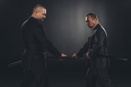 Side view of businessmen taking out katana swords for fight isolated on black Stock Photo