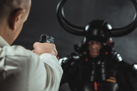 Close-up shot of man aiming on armored samurai with gun