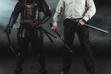 Cropped shot of modern man and samurai with katana swords on black Stock Photo