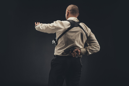 Security man showing stop sign and holding gun behind back Stock Photo