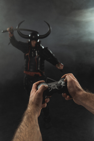 Cropped shot of man controlling samurai character with gamepad on black Imagens