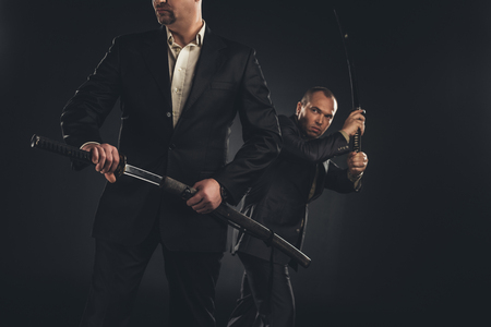Two mature modern samurai with katanas isolated on black Stock Photo