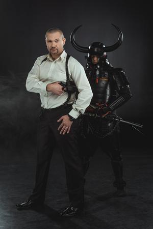 Man with gun and samurai behind him on black