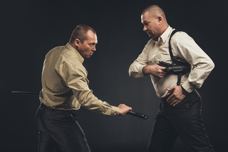Side view of men fighting with gun and katana sword on black