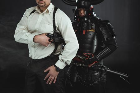 Cropped shot of man with gun and samurai behind him on black