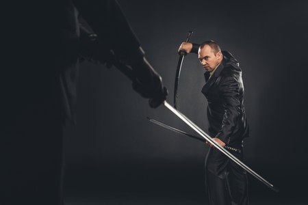 Mature modern samurai in suit ready to fight on black Stock Photo