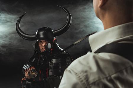 Angry samurai with katana ready to kill modern man