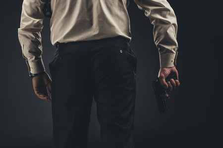Cropped shot of man holding gun in hand Stock Photo