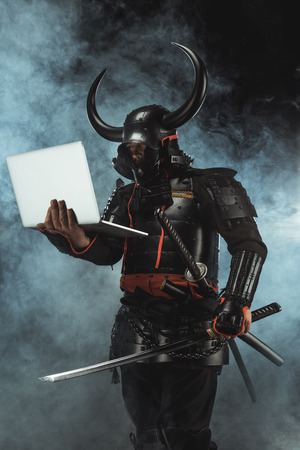 Samurai in traditional armor holding laptop on dark background with smoke Stok Fotoğraf - 112770580