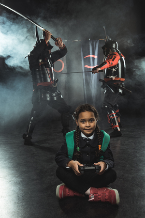 Little schoolkid playing samurai fighting with gamepad in real life Stock fotó