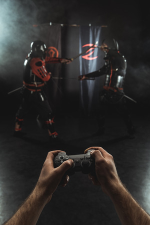 Cropped shot of playing samurai fighting with gamepad in real life