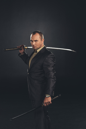 Handsome man in suit with katana sword isolated on black Stock Photo
