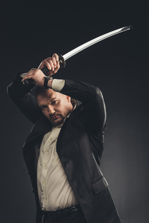 Serious mature man in suit with katana sword isolated on black