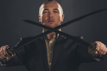 Close-up shot of man in suit with katana sword on black