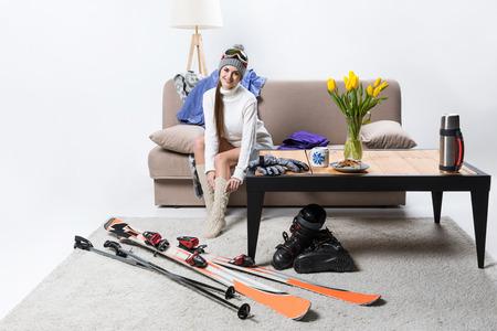 Young sportswoman wearing warm socks, ski equipment near