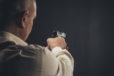 Close-up shot of security man aiming with gun Stock Photo