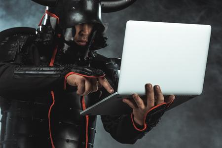 Close-up shot of samurai using laptop on dark background with smoke