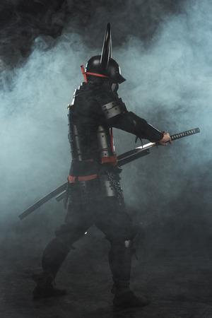 Side view of samurai taking out his katana on dark background with smoke 版權商用圖片