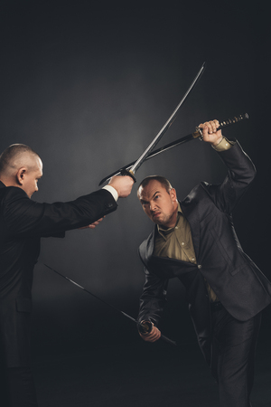 Modern samurai in suits fighting with swords on black