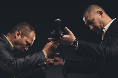 Modern businessmen passing katana sword isolated on black