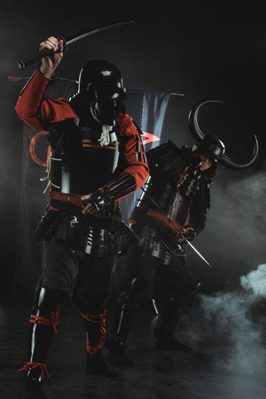 Armored samurai fighting with swords in front of clan symbols on flags on black Stok Fotoğraf