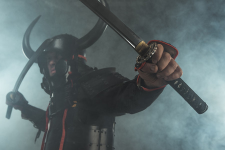 Close-up shot of samurai in armor with dual katana swords on dark background with smoke Foto de archivo