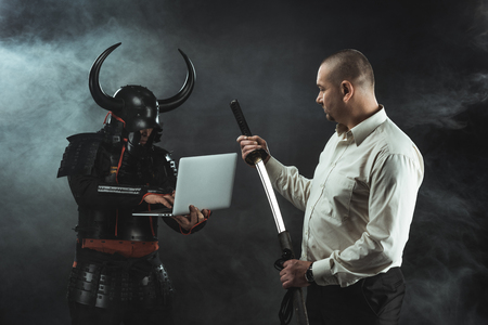 Man with katana standing in front of samurai while he using laptop