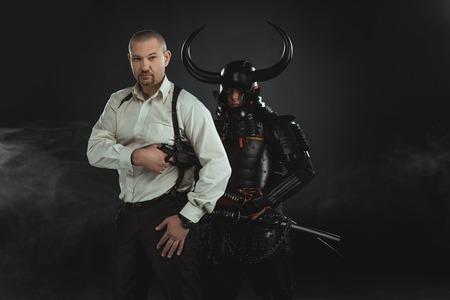 Man with gun and armored samurai behind him on black