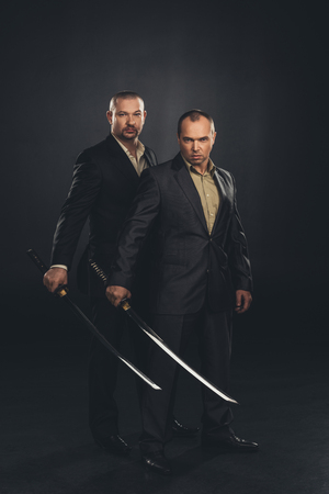 Businessmen with katana swords isolated on black Stock Photo