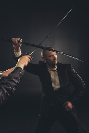Strong mature businessman fighting with katana sword isolated on black Stok Fotoğraf