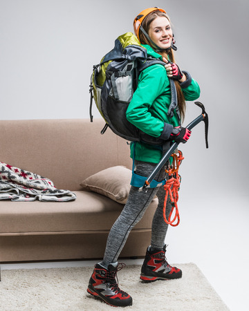 Young happy climber with backpack, ice axe and climbing rope at home