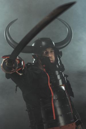 close-up shot of samurai in traditional armor with katana sword on dark background with smoke Standard-Bild - 112768799