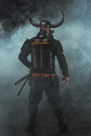 rear view of samurai in traditional armor on dark background with smoke