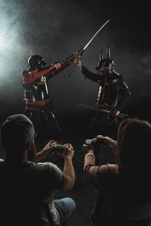 back view of man and woman playing samurai fighting in real life with gamepads on black