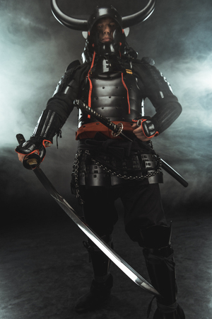 samurai in traditional armor with swords on dark background with smoke Stock Photo