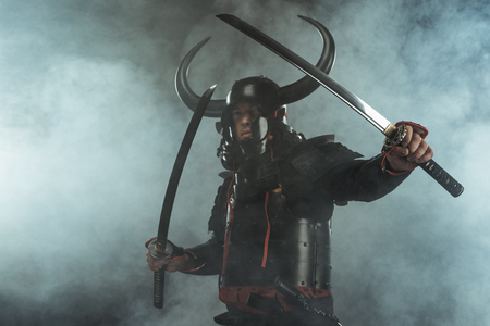 samurai in traditional armor with dual katana swords in defence position on dark background with smoke Stock Photo