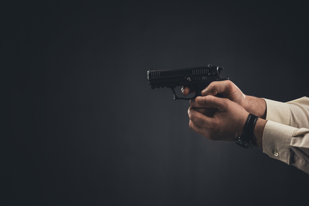 cropped shot of man holding gun isolated on black Stok Fotoğraf - 112769802