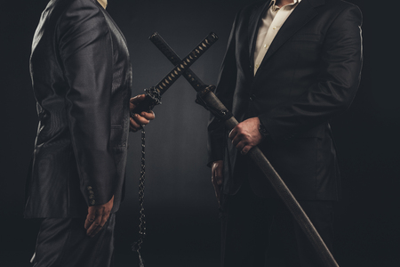 cropped shot of meeting of modern samurai in suits with katana swords isolated on black