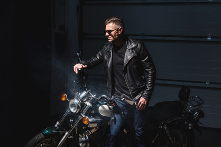 fashionable guy in black sunglasses standing by motorcycle in garage Stock Photo