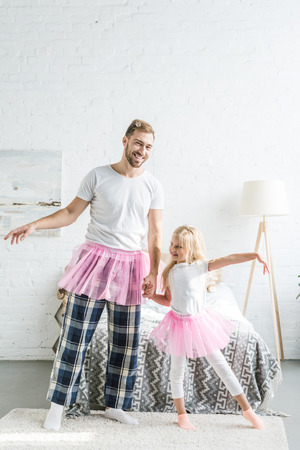happy father and adorable little daughter in pink tutu skirts holding hands and dancing at home