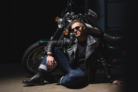 handsome biker in sunglasses standing by motorcycle in garage Stock Photo