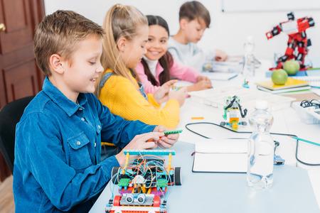 gelukkige kinderen die aan het bureau zitten en robots maken in de klas voor stamonderwijs