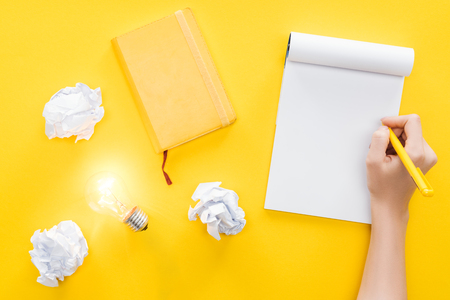 bijgesneden weergave van vrouw schrijven in blanco notitieboekje, verkruimelde papieren ballen en gloeiende gloeilamp op gele achtergrond, met nieuwe ideeën concept Stockfoto