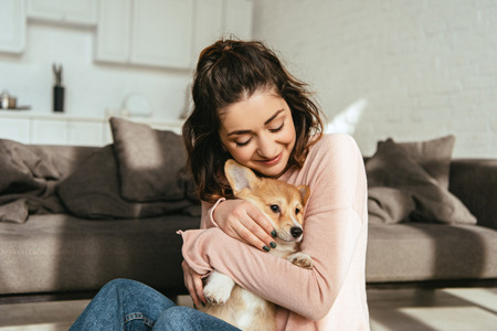 beautiful woman embracing cute welsh corgi pembroke at home